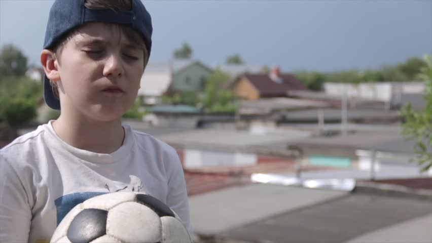 7 year-old Russian white boy in cap with closed eyes and a soccer ball in his hands praying for football team on the background of provinicial Russian urban city garages. Football children education   Shutterstock HD Video #1012552907