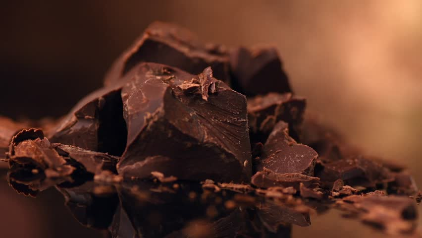 Chocolate, Pieces, Chunks of sweet dark chocolate rotated on brown background close-up. Gourmet dessert ingredient. Confectionery, confection concept. Slow motion 4K UHD video