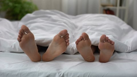 Womans feet flirting with man in bed, couple having intimate problem, relations