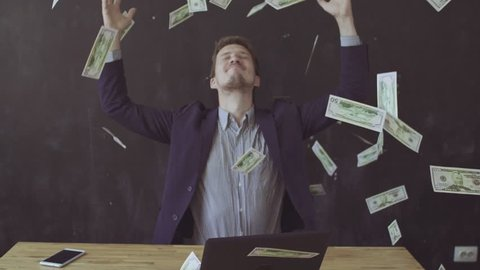 Happy man enjoying the rain of money. Banknotes flying in the air