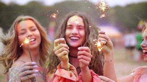 Young people having fun with sparklers during at the festival