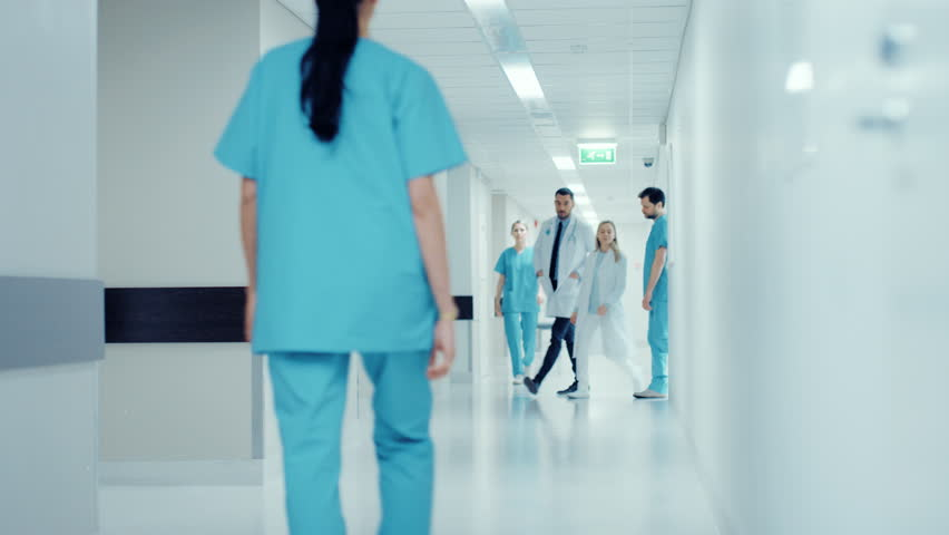 Team of Doctors, Surgeons and Nurses Walk Through Busy Hospital Hallway, They Talk about Patients, Forthcoming Surgeries and Saving Lives. Clean Modern Hospital with Professional Staff. 4K UHD.   Shutterstock HD Video #1012593677