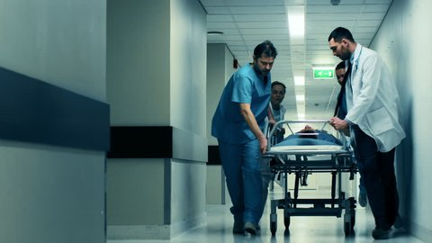 Emergency Department: Doctors, Nurses and Paramedics Push Gurney / Stretcher with Seriously Injured Patient towards the Operating Room. Shot on RED EPIC-W 8K Helium Cinema Camera.