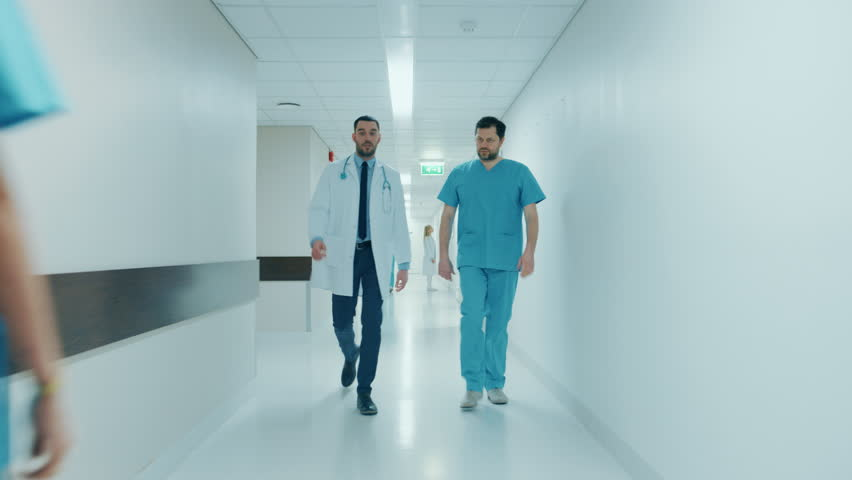 Surgeon and Doctor Walk Through Hospital Hallway in a Hurry while Talking about Patient's Health. Modern Bright Hospital with Professional Staff. Shot on RED EPIC-W 8K Helium Cinema Camera. | Shutterstock HD Video #1012593947