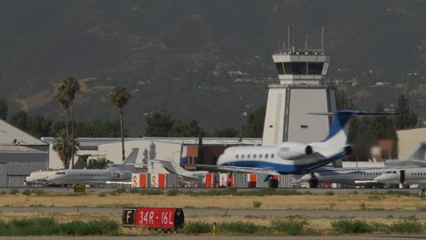 PRIVATE JET TAKES OFF NEAR CONTROL TOWER.  SHOT IN 4K THROUGH HEAVY HEATWAVES.