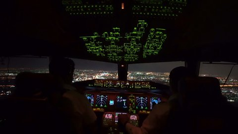 Two pilot were operating the airplane in approach phase toward the runway in airport at night, can see beautiful view of cityscape and lights of runway from inside cockpit.