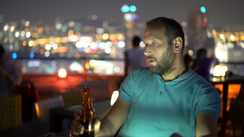 Sad, unhappy man drinking beer in skybar at night  | Shutterstock HD Video #1012642427