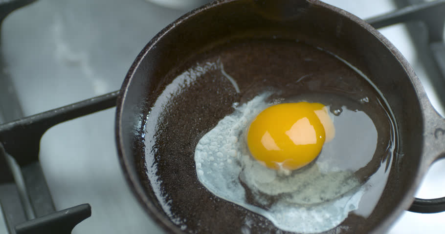 Close up of messy egg being cracked open and fried in a saucepan. 4k footage.