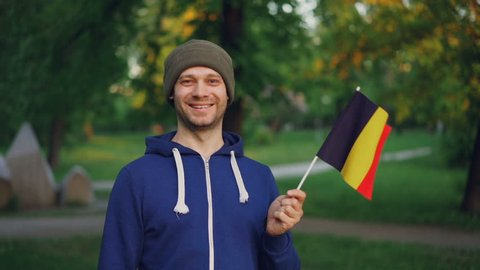 Slow motion portrait of Belgian man in sports jacket and hat holding national flag of Belgium with happy smile and looking at camera. People and nationality concept.