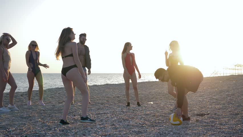 Beach sports, company of friends playing with ball in volleyball on shore ocean in backlight | Shutterstock HD Video #1012673837