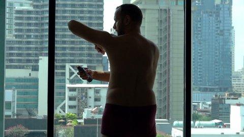 Man applying antiperspirant on armpit by window, slow motion shot at 240fps