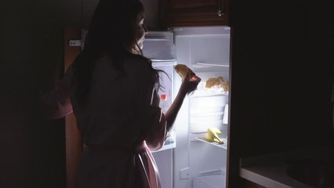 Young woman opens the fridge at night.