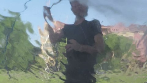 Man washing car with cleaning foam and high pressured water, viewed from the inside of the vehicle
