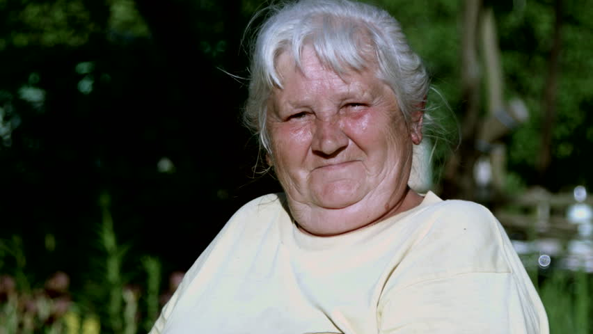 Portrait of an elderly woman in the garden, who makes faces looking at the camera. | Shutterstock HD Video #1012718867