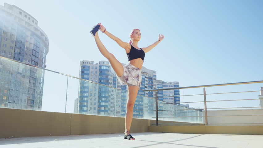 Young slim woman with pink dyed hair doing yoga practice on terrace of modern city. Slow motion. Girl keeping fit and healthy body relaxing on rooftop during practice pose