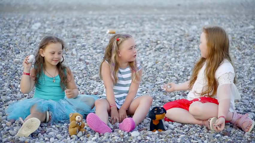 three cute little girl are sitting on a gravel beach in evening, playing and chatting to each other