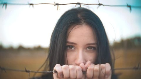 girl brunette refugee behind barbed wire camp slow motion video. lifestyle the concept of freedom is upset Woman hands and barbed wire. girl Refugee, prison, refugees captivity concept