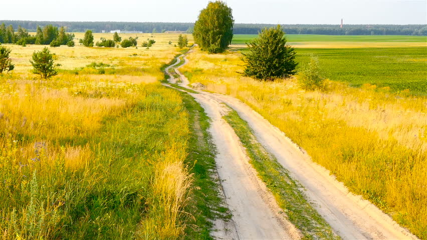 A long and winding road in the field. Picturesque landscape. The camera goes down