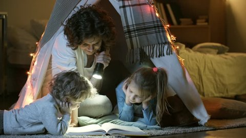 Two little children of primary school age looking at book of fairy tales when sitting in teepee play tent with loving mother