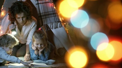 Tracking shot of young curly haired mother holding flashlight and reading aloud to children of elementary school age when sitting in teepee play tent at night