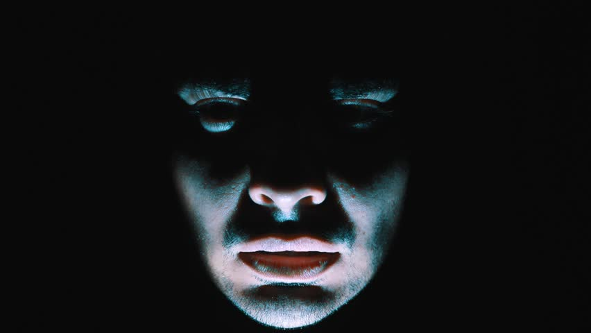 Nightmare shot of a demon face in the darkness moving around screaming and being scary while a light flashes on his face to add drama to the scene