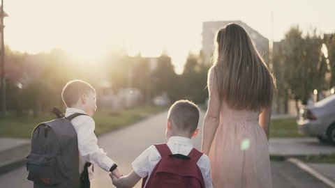 Tracking: Young mother goes with the children with school children, they tell her about successes, she smiles and praises them, raises her finger up.