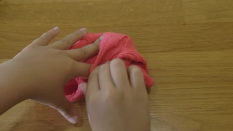 Slow motion (60fps) - Red slime stretched in the hands of a young child