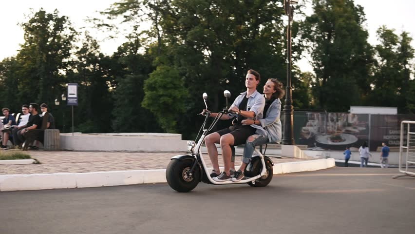 Young man and her girlfriend are riding an electric bile in the crowdy green park. Wearing casual. Happy moments, enjoying life