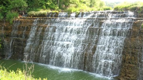 Real time view of the beautiful Thunder Bay Waterfall with water pouring over the rocky stepped cliff located along a road in Galena Illinois.