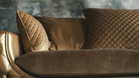 Luxury golden sofa on a loft background