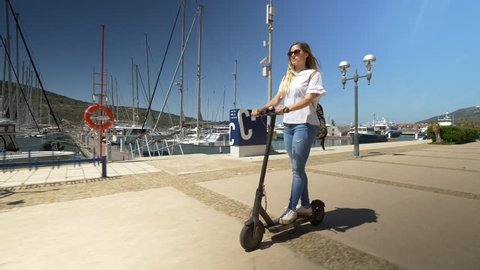 Full shot - Female riding electric scooter through marina. Modern transportation gadget and popular futuristic device among young people