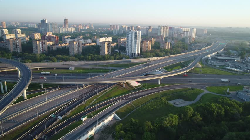 Aerial view. Flyght around a huge interchange of the Moscow ring road in the early morning at dawn. Cars are moving on a multi-level road junction.Highway are free for them moves few cars. | Shutterstock HD Video #1012887467