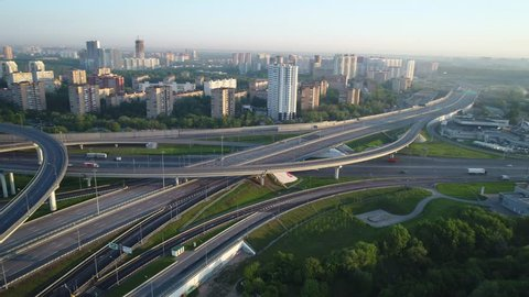 Aerial view. Flyght around a huge interchange of the Moscow ring road in the early morning at dawn. Cars are moving on a multi-level road junction.Highway are free for them moves few cars.