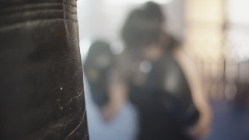 Close up of a boxing glove hitting a punching bag. Female boxer at slow motion. #10128887