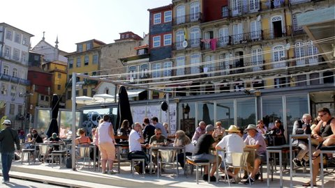 PORTO, PORTUGAL - CIRCA JUNE, 2018: Typical houses and outdoor cafes at historic Ribeira Square of Porto