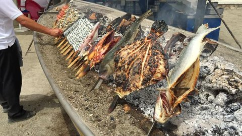 "Sardine, shrimp, squid on sticks on fire are fried in a boat. Typical ""espetos"" food of Spain, Costa del Sol, Malaga. Traditional food."