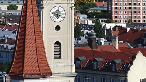 Extreme long shot of St. Peter's Church clock tower in Munich, Germany on a bright sunny day with blue sky ZOOM OUT