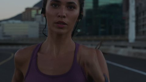 close up fit hispanic woman running on city street training intense cardio endurance workout focused female runner enjoying evening run slow motion