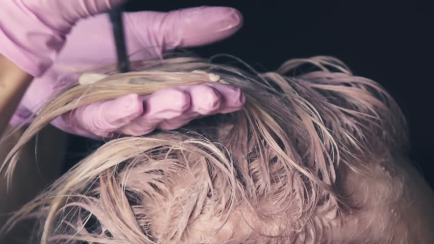 Dyeing light strands of hair. creating a blond shade on the hair. styling hair on the head | Shutterstock HD Video #1012928627