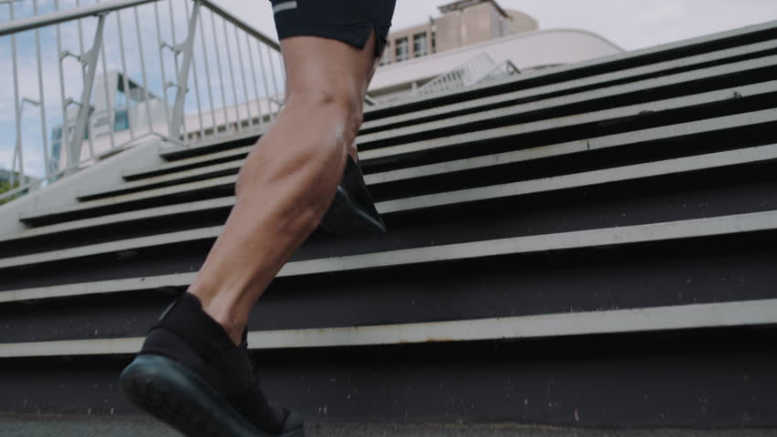 Young man athlete legs running up stairs training intense cardio workout exercise male runner feet jogging on steps in urban city background slow motion