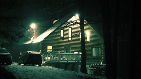 Cozy cabin on a snowy night with all the lights on looking warm and inviting during a blizzard in Kentucky in wintertime one color corrected for night cinematic imagery, the other no color correction.