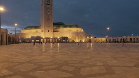Camera tilt up reveal from tiled square floor to Hassan II Mosque minaret with night lights in Casablanca, Morocco