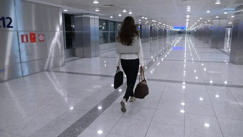 Business woman walks at empty passage at sterile area of airport, follow tracking camera.