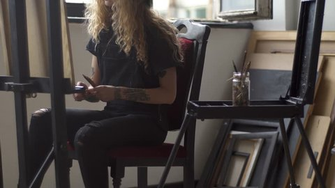 Talented female student doing home assignment, fair-haired girl drawing a picture near studio window on clear warm day, holding a few pencils as working on the project
