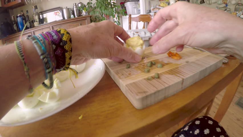 Woman making deviled eggs that look like chickens in a shell for Easter with capers for eyes and carrots for a nose - POV
