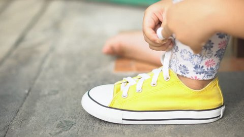 hand of children or kid girl learning and try tie yellow shoe laces or sneakers rope and footwear for walk travel and fashion on street with independent and free on 4K