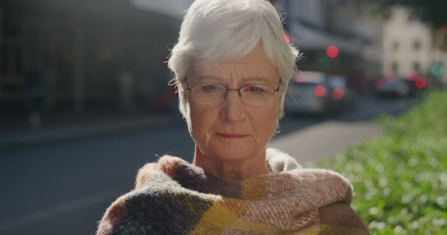 Portrait of beautiful elderly woman looking sad lonely worried retired female unhappy expression in urban city street background wearing glasses | Shutterstock HD Video #1012992407