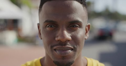 portrait close up of african american man smiling cheerful looking at camera enjoying summer vacation in urban city waterfront handsome black male happy satisfaction slow motion