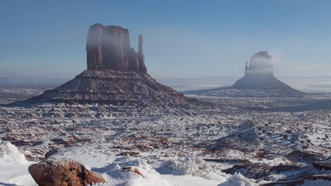 4K time lapse of low fog clouds, blue sky and sunlight on snow covered Mittens geological rock formations in Monument Valley in Navajo Nation, Arizona after a rare strong winter snow storm