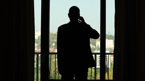 Man in casual suit stay silhouetted against window, rise hand with smartphone and answer on phone call. Half length slow motion shot, sunny city seen outdoors.
